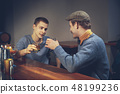 Two young men in casual clothes sitting at bar counter in pub 48199236