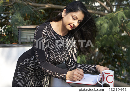 Pretty woman writing in diary 48210441