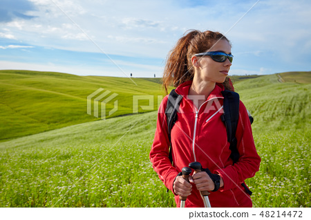 Tourist woman with backpack hiking in the mountains on field 48214472