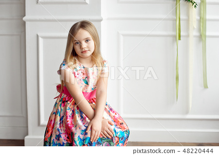 Portrait of little smiling girl child in colorful dress posing indoor 48220444