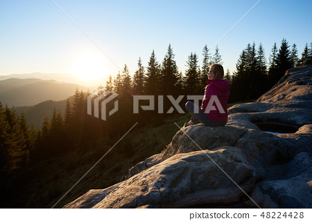 Woman hiker sitting on boulder in the mountains at sunset 48224428