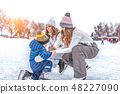Young mother, two women, girlfriends raise son boy for 2-3 years, ice skating rink in winter city 48227090