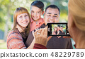 Woman Takes Photo of Hispanic Mixed Race Family 48229789
