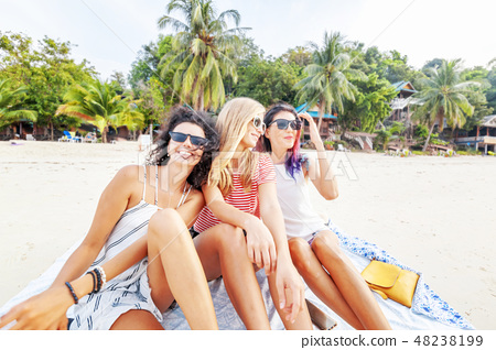 Three young beautiful girlfriends relax and have fun on a tropical beach, travel and vacation 48238199