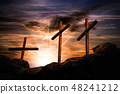 Three crosses on a dramatic sky at sunset 48241212