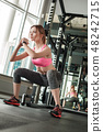 Young girl in gym healthy lifestyle squatting concentrated 48242715