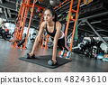 Young woman in gym sporty lifestyle standing in plank pose on mat concentrated 48243610