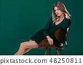 blonde woman posing in green dress on green background 48250811