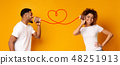 Young black couple with can phone on orange background 48251913