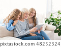 Granny, mother and child using digital tablet at home 48252324