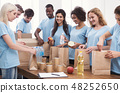 Volunteers putting food and drinks into paper bags 48252650