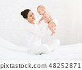 Young mom holding her happy baby in air 48252871