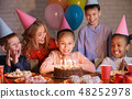 Happy children looking at birthday cake with candles 48252978