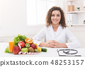 Dietitian working on diet plan at office, smiling at camera. 48253157