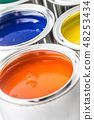 Full of multicolored paint cans on white table 48253434