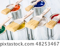 Close-up brushes lying on multicolored paint cans. 48253467