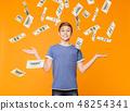 Little boy enjoying money rain on orange background 48254341