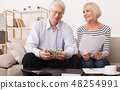 Senior couple calculating budget with papers and calculator 48254991