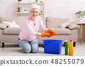 Smiling mature housewife cleaning floor at home 48255079