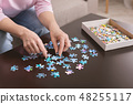 Elderly woman hands doing jigsaw puzzle closeup 48255117