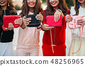 Smiling girlfriends with manicure holding handbags 48256965