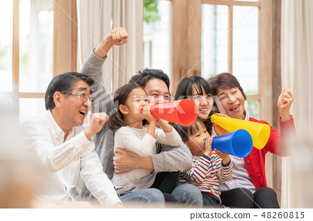 A happy three generation family watching the Olympic Games and supporting all six members of the family 48260815