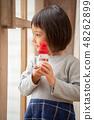 เด็กหญิงอนุบาลที่น่ารักแสดงให้ฉันเห็นตุ๊กตาหิมะสำหรับคริสต์มาสที่ทำจากยาคุล 48262899