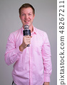 Happy young handsome businessman as host with microphone 48267211
