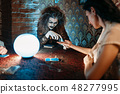Foreteller guessing by hand over a crystal ball 48277995
