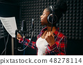 Young woman songs in audio recording studio 48278114