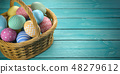 Easter eggs in a basket on the green wooden planks 48279612