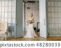 The bride stands at the open door in a beautiful wedding dress and a bouquet of flowers 48280039