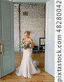 The bride in a beautiful wedding dress looks at the wedding bouquet 48280042