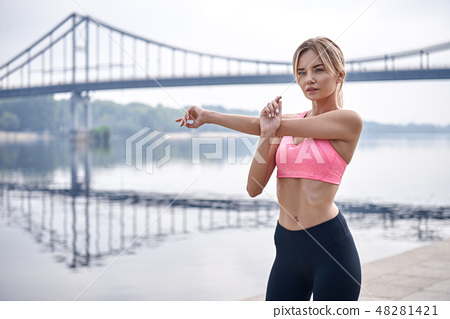 Morning warming up before workout. Handsome young womanin sports clothing stretching while warming 48281421