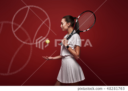 Talk with your raquet, play with your heart. Young tennis player standing isolated over red 48281763