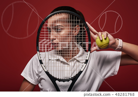 Believe Achieve. Young tennis player standing isolated over red background with a racket and a ball 48281768