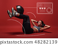 Best exercise. Sportswoman lying over red background, working her abs 48282139