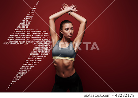 Full of energy. Sportswoman standing over red background, looking away 48282178
