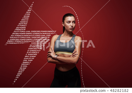 Ready to break any record. Sportswoman standing over red background, looking away 48282182