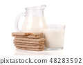 jug and glass of milk with grain crispbreads isolated on white background 48283592