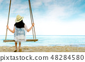 Asian woman wear hat and sandals sit on swings  48284580