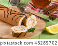 Biscuit swiss roll with a cup of tea on green wooden background 48285702