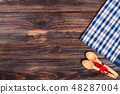 blue checkered tablecloth on the black wooden table with copy space for your text. Top view 48287004