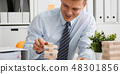 Businessman plays in a strategy of jenga hand 48301856