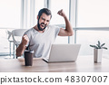 Handsome dark-haired businessman celebrating success with arms raised while looking at his laptop 48307007