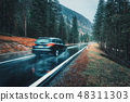 Blurred car in motion on a road in forest in rain 48311303
