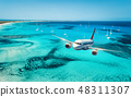 Airplane is flying over islands and sea at sunrise 48311307