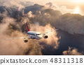 Airplane is flying over mountains and low clouds  48311318