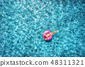 Woman swimming on pink donut swim ring in blue sea 48311321
