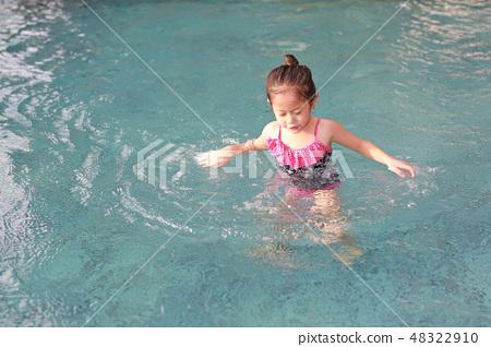 Asian child girl has fun playing in the pool. 48322910